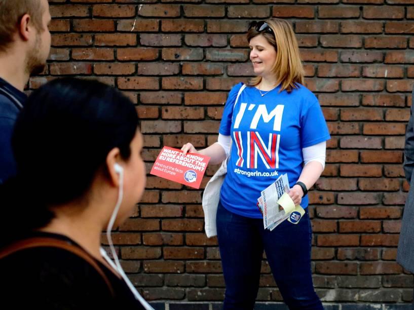 Mulher distriubui panfletos em favor da permanência do Reino Unido na União Europeia, em Londres