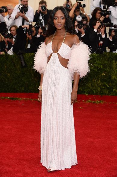 Naomi Campbell engrossa a lista das mais mal vestidas do MET 2014 com o look branco de penas