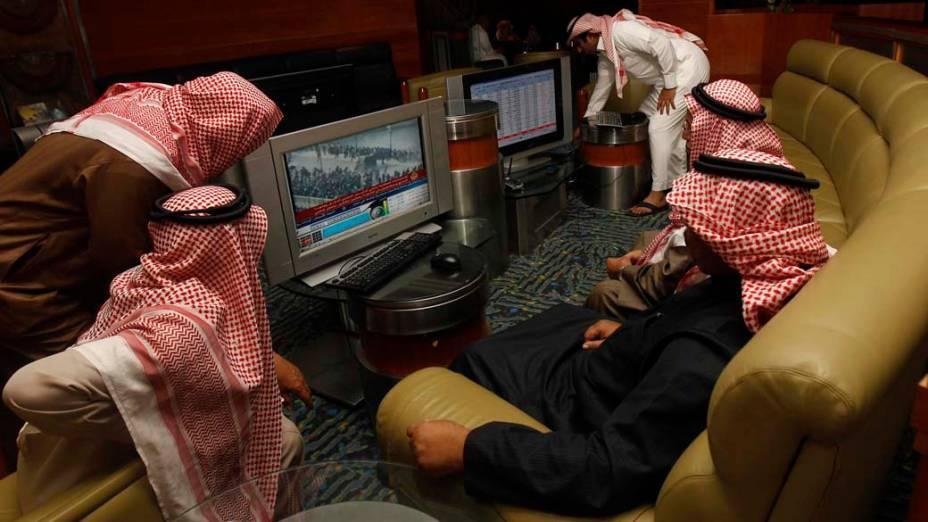 Investidores sauditas assistem noticiário sobre a situação do Egito na cidade de Riad