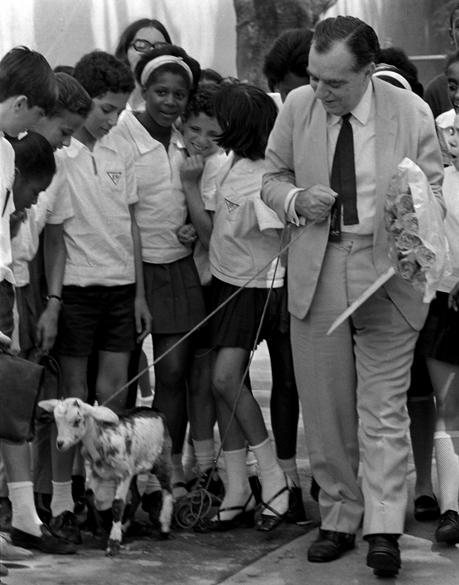 """O jornalista e escritor Nelson Rodrigues recebe homenagem de alunos da Escola Gonçalves Dias e ganha de presente uma cabra (alusão ao quadro """"Cabra Vadia"""", do programa """"Noite de Gala"""") e flores, em 1969"""