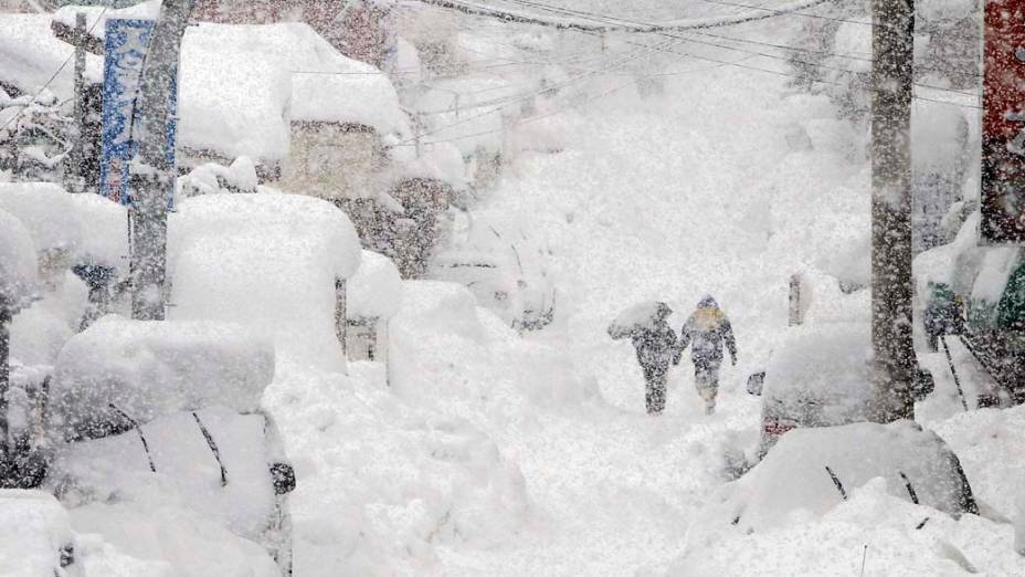 Casal caminha por rua coberta de neve na cidade de Gangneung, Coreia do Sul