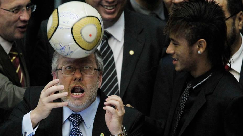 Marco Maia, presidente da Câmara dos Deputados arrisca embaixadas ao lado do jogador Neymar durante sessão em homenagem ao centenário do Santos em Brasília