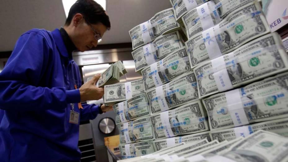 Funcionário de banco coreano conta notas de dólar em Seul, Coréia do Sul