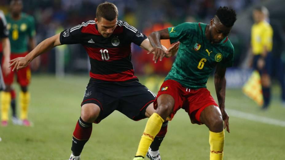 O alemão Lukas Podolski disputa a bola com o camaronês Alexandre Song. A partida terminou dois a dois<br><br>