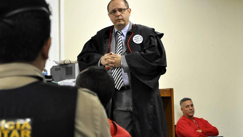 O detento Jailson Oliveira presta depoimento acompanhado por um policial