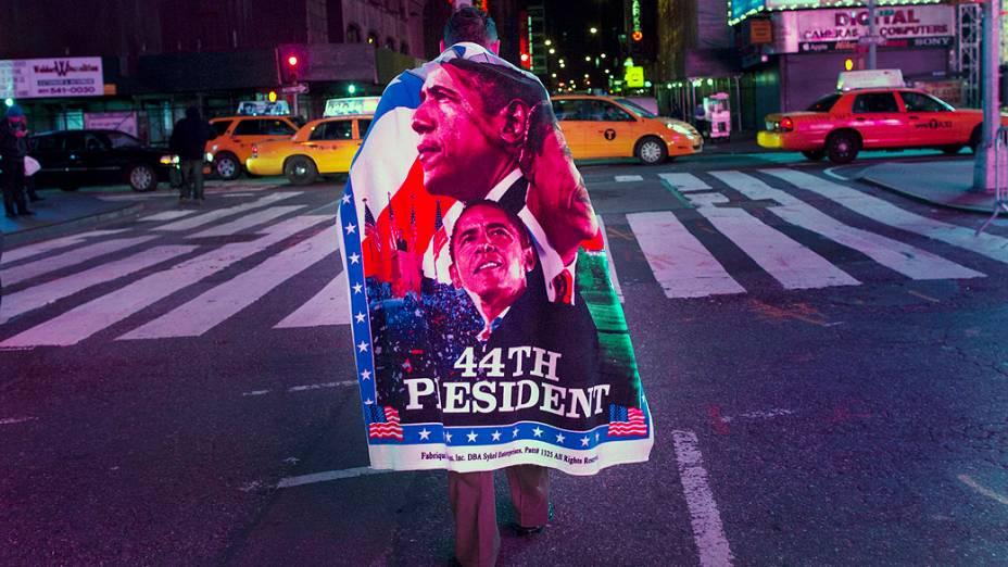 Eleitor na Times Square em Nova York enrolado em uma bandeira de Barack Obama