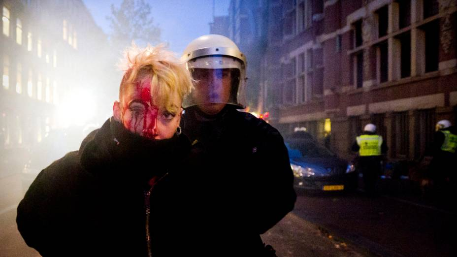 Em Amsterdã, Holanda, policial prende morador que vivia em imóvel abandonado. Nesta sexta, houve manifestações contra a proibição da ocupação dos imóveis