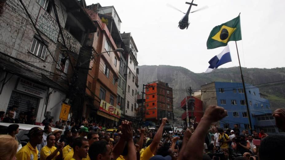Militares e moradores acompanham a cerimônia de hasteamento das bandeiras na favela da Rocinha, no Rio de Janeiro