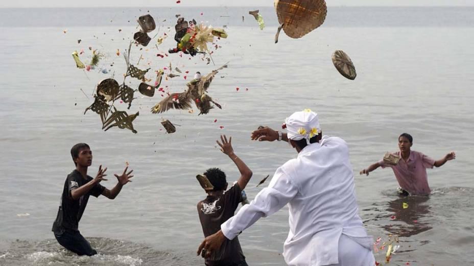 """Hindus jogam oferendas no mar durante o festival """"Melasti"""", em Sanur, Indonésia"""
