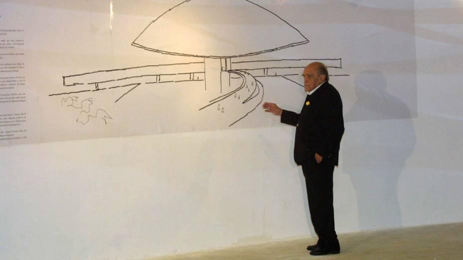 2002 - Oscar Niemeyer posa em frente a reprodução de um dos seus desenhos