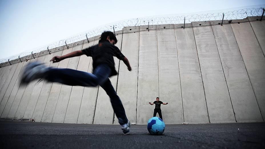 Crianças palestinas jogam bola em frente ao muro construído por Israel ao redor dos territórios palestinos, na vila de Abu Dis, Cisjordânia