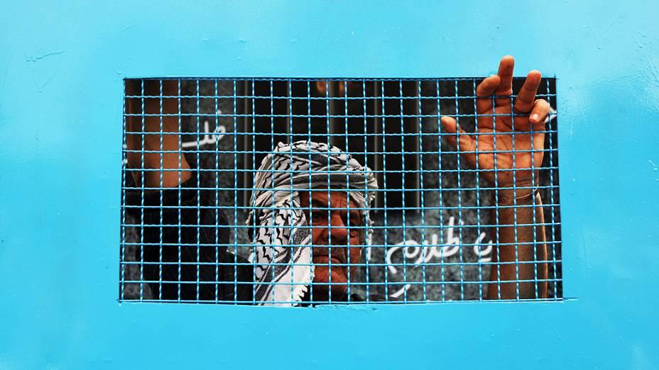 Homem palestino está acorrentado a uma gaiola durante uma manifestação na cidade de Ramallah, na Cisjordânia