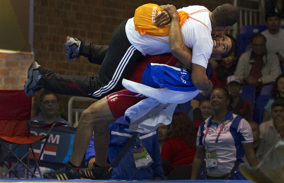 Brea Anyelo Mota da República Dominicana comemora, com seu técnico, vitória sobre o mexicano Ulises Barragan em partida de luta livre, no sexto dia dos Jogos Pan-Americanos em Guadalajara, México, em 20/10/2011