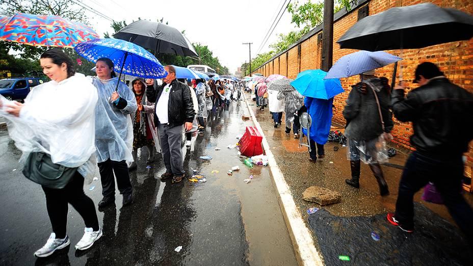 Fiéis aguardam a chegada do papa Francisco debaixo de chuva em Aparecida do Norte