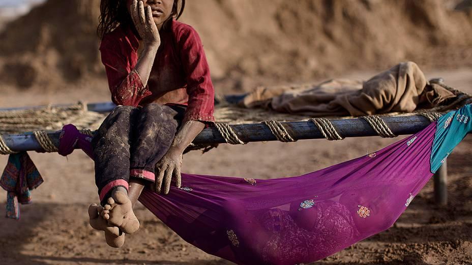 Criança paquistanesa, que trabalha em uma fábrica de tijolos, descansa em uma cama ao lado de sua irmã. O Dia Mundial Contra o Trabalho Infantil é comemorado nesta terça-feira
