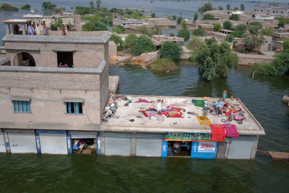 Vítimas das enchentes no Paquistão sobem nos telhados para receber alimentos do exército local em Khairpur Nathan Shah.