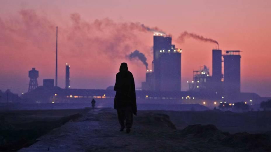 Homem caminha próximo à fábrica de fertilizante em Multan, Paquistão
