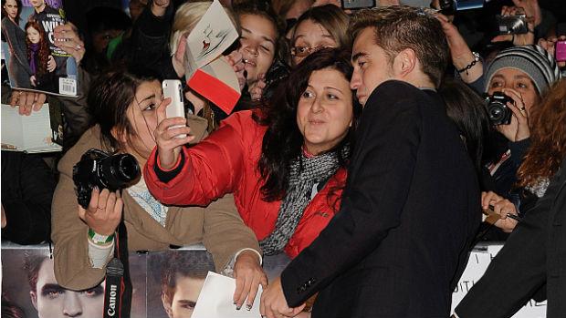 O ator Robert Pattinson tira foto com fãs durante première de Amanhecer - Parte 2 em Londres