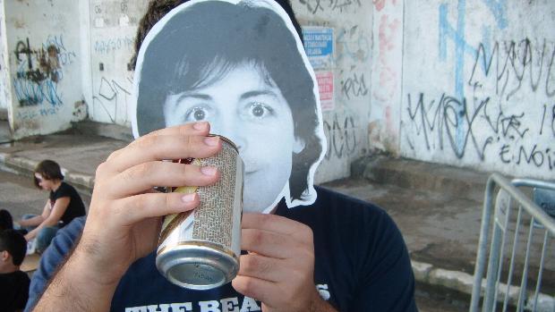 Fã veste máscara de Paul McCartney à espera do show, no Recife