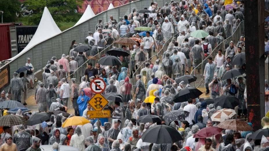 Fãs se protegem da chuva na entrada para o segundo dia do show de Paul McCartney no estádio do Morumbi, São Paulo/SP