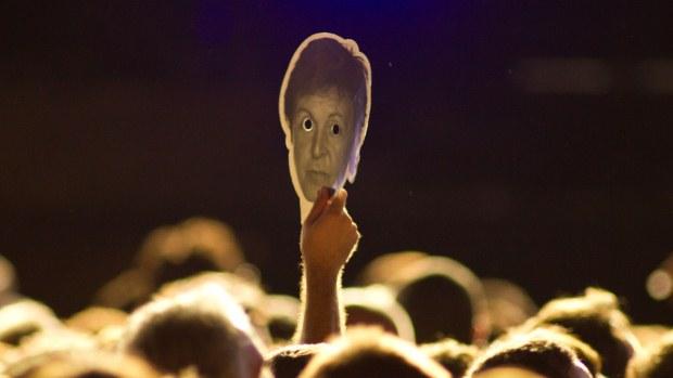 O público levou máscaras com a rosto do ex-Beatle para o show