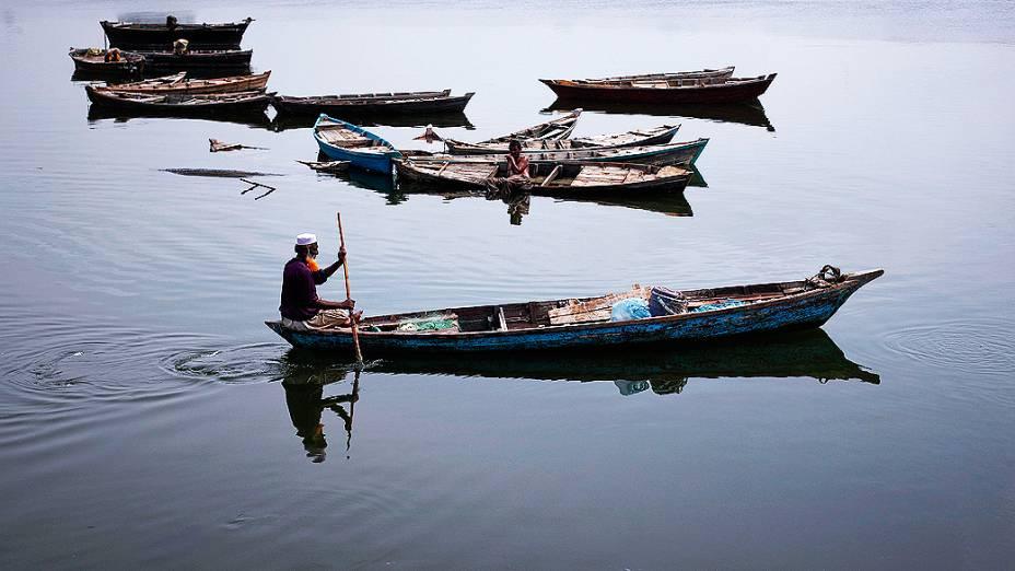 Pescador rema seu barco em um lago aos arredores de Karachi, no Paquistão