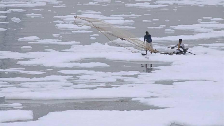 Pescadores lançam rede nas águas poluídas do rio Yamuna em Nova Déli, na Índia