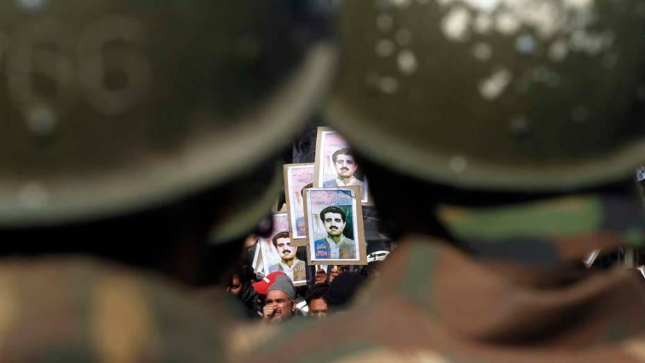 Policiais olham para membros da Frente de Libertação da Caxemira em Srinagar, Índia