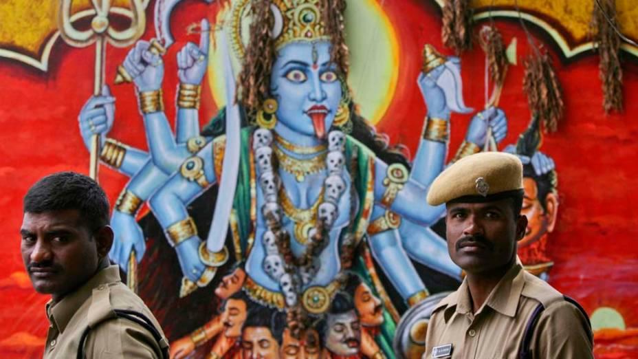 Policiais em frente a imagem da deusa hindu Kali, em templo em Hyderabad, Índia