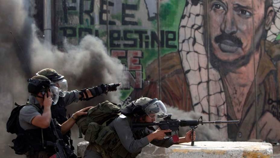 Policiais israelenses durante conflito com manifestantes no território palestino de Qalandiya