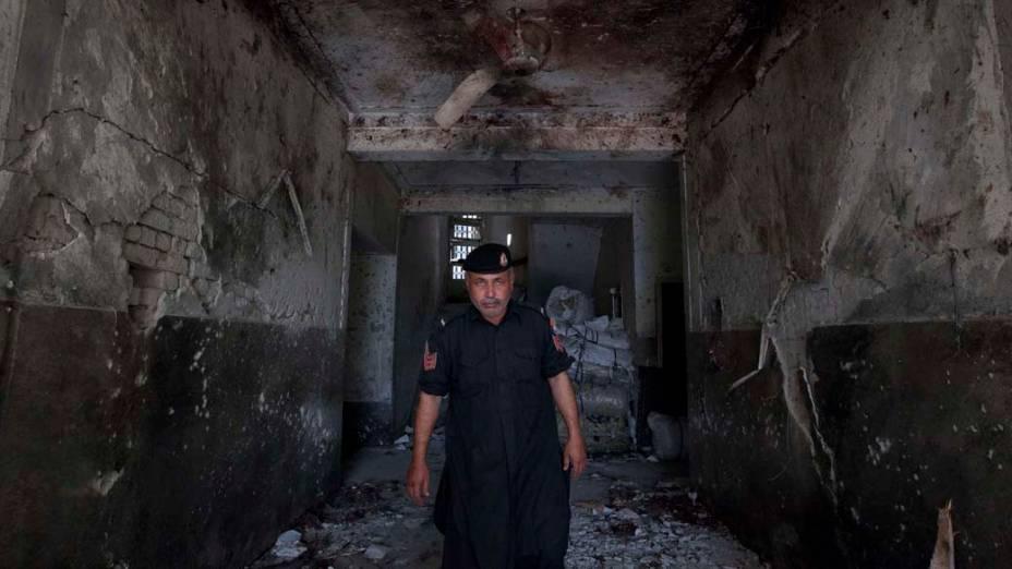 Policial caminha entre os escombros de edifício destruído por um atentado suicida em Swabi, no Paquistão