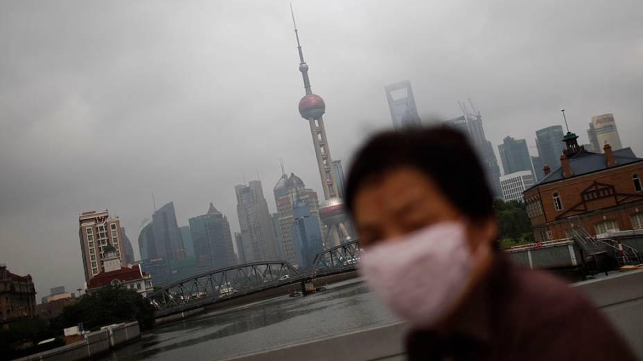 Mulher de máscara caminha ao longo do rio Huangpu. Xangai é uma das cidades mais poluídas do mundo por causa do gás carbônico e do sulfeto