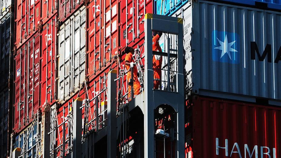 Funcionários inspecionam contêineres em processo de armazenamento, no Porto de Santos