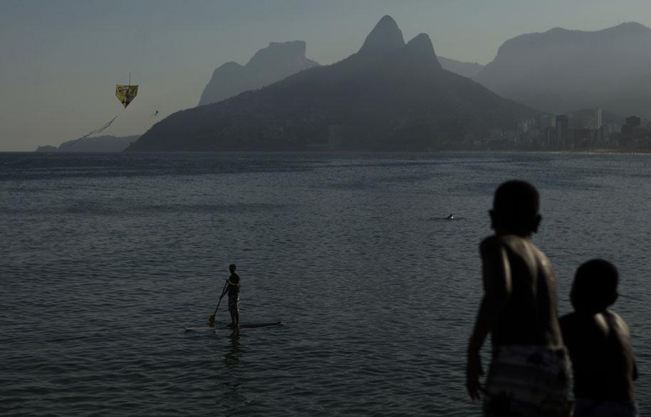 Crianças empinam pipa na praia do Arpoador, no Rio de Janeiro