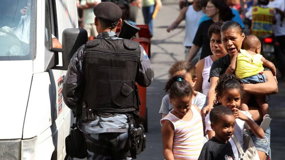 Moradores circulam normalmente, enquanto policiais do Batalhão de Choque monitoram as saídas da Rocinha, no Rio de Janeiro - 11/11/11