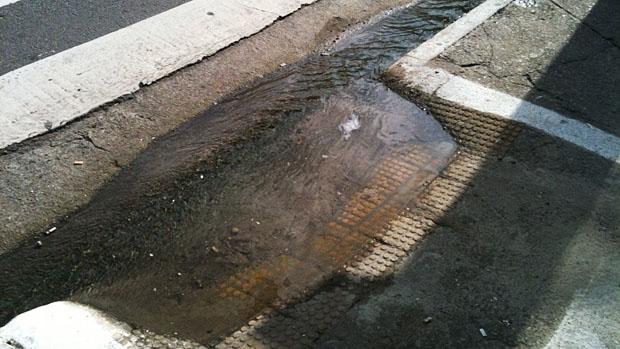 Água acumulada entre a rua e a rampa de acessibilidade. Mais uma dificuldade enfrentada por cadeirantes
