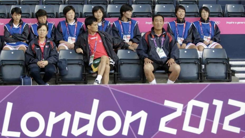 Jogadoras da seleção norte-coreana aguardam a resolução da crise provocada pela exposição da bandeira errada no jogo desta quarta, em Glasgow