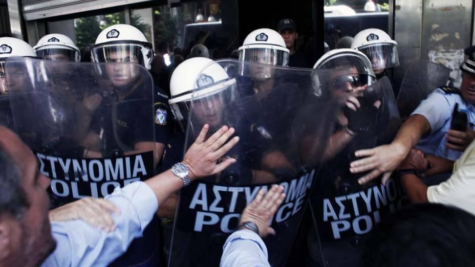 Em Atenas, conflito entre policiais e manifestantes em frente ao Ministério das Finanças. O ministro anunciou que a Grécia receberá outra parcela da ajuda da dívida até o próximo mês