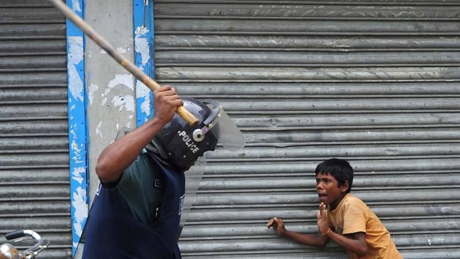 Em Bangladesh, policial ameaça um garoto com um bastão. Pelo menos 15.000 empregados da indústria têxtil saíram às ruas para protestar contra os baixos salários e más condições de trabalho