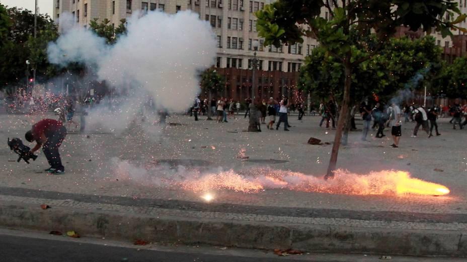 Repórter cinematográfico da TV Bandeirantes larga a câmera e cai no chão por causa do impacto do explosivo