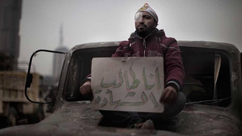 """Manifestante ferido mostra cartaz """"Quero ser mártir"""", escrito em árabe, em uma barricada do exército"""