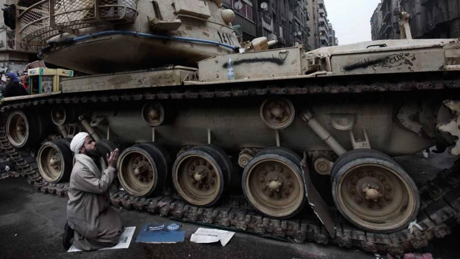 Manifestante reza ao lado de um tanque do exército egípcio durante o 12º dia de protestos no Cairo, Egito