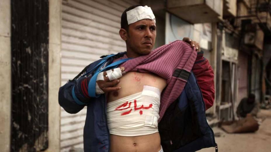Manifestante anti-governo mostra ferimentos com o nome do presidente Hosni Mubarak escrito em suas ataduras