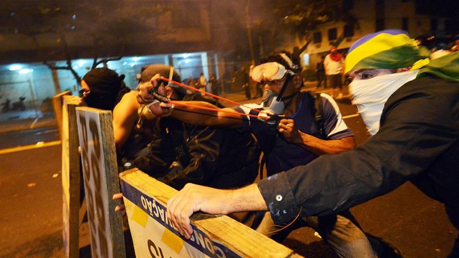 Manifestantes atirando pedras contra policia durante protesto em uma rua perto do estádio do Maracanã do Rio de Janeiro