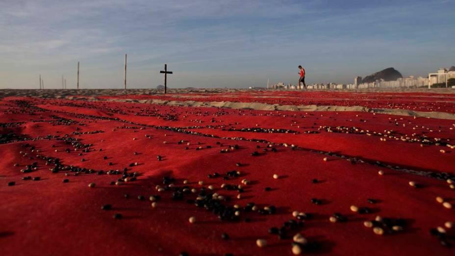 Cerca de 500.000 feijões foram colocados sobre folhas vermelhas para representar o número de pessoas mortas nos últimos 10 anos no Brasil, no Rio de Janeiro