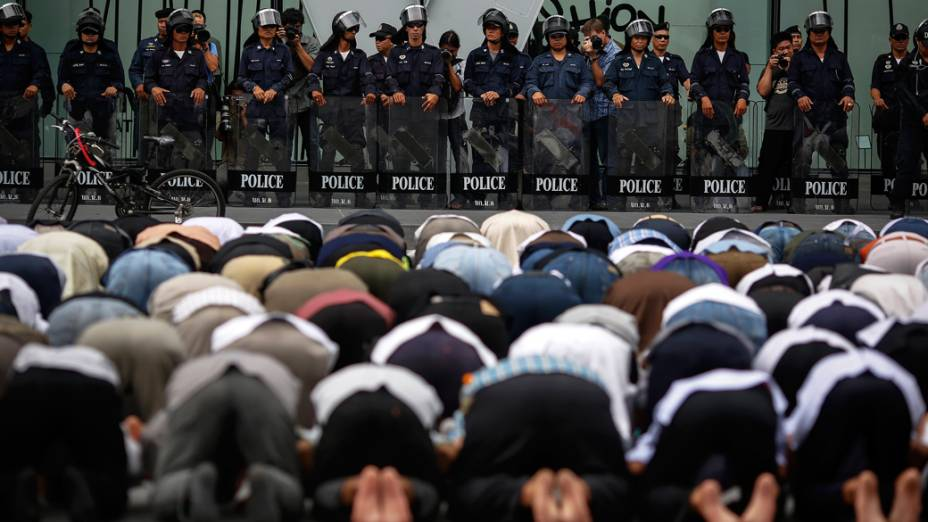 Policiais em guarda em frente a embaixada americana onde manifestantes mulçumanos protestam contra o filme Inocência dos mulçumanos em Bangcoc, Tailândia