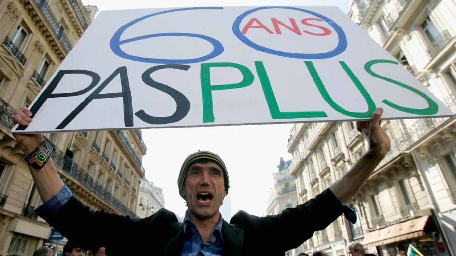 """Com um cartaz escrito """"60 anos não mais"""", homem protesta nas ruas de Paris contra reforma da previdência proposta pelo governo francês"""