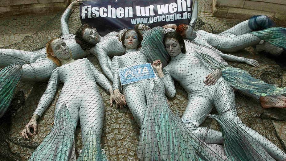 Integrantes do grupo de defesa dos animais PETA se cobrem de redes como peixes durante um protesto em Dusseldorf, na Alemanha, contra o uso de redes de arrasto nos oceanos