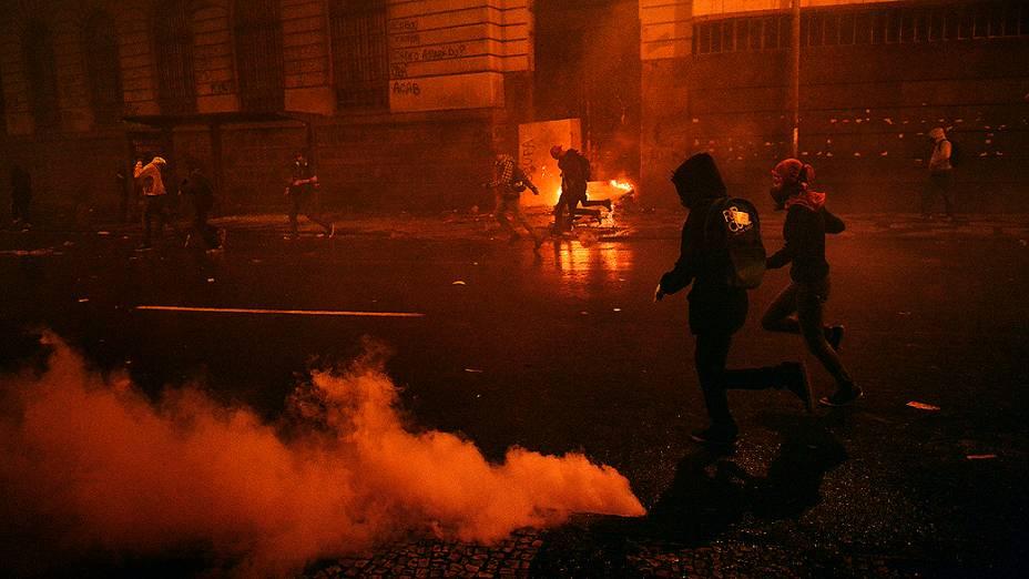 Rio de Janeiro - Manifestantes correm em meio a bombas de gás lacrimogêneo disparadas pela polícia na sequência de confrontos após manifestação pacífica de professores ser invadida por grupo de mascarados - (07/10/2013)