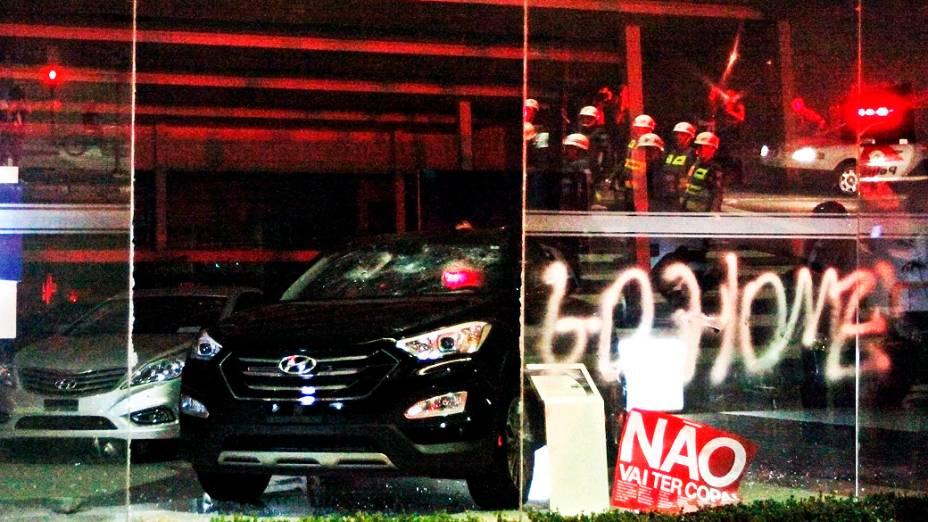 Carros de concessionárias que ficam nos arredores da avenida Paulista são danificados por manifestantes durante protesto contra os gastos na Copa, nesta quinta-feira (15)